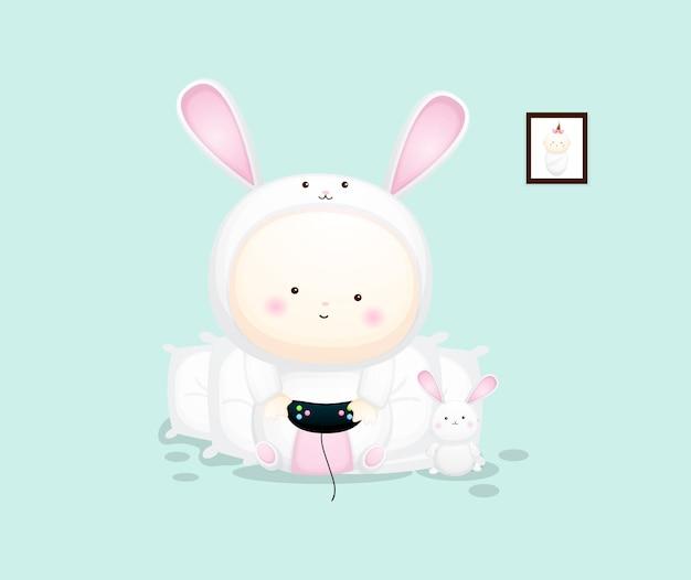 Lindo bebé en traje de conejito sosteniendo juegos. ilustración de dibujos animados vector premium
