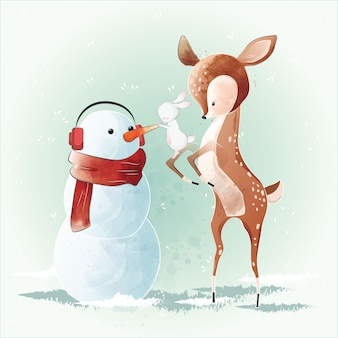 Lindo ciervo construyendo un muñeco de nieve