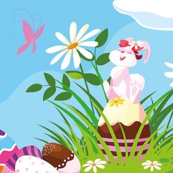 Lindo conejo hembra con huevos de pascua en el jardín