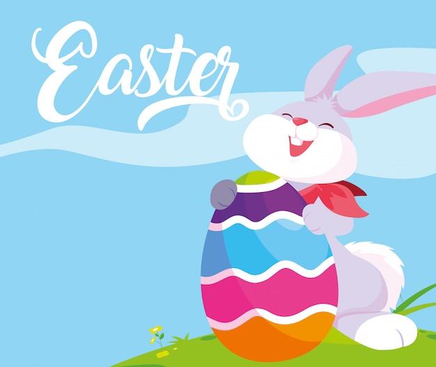 Lindo conejo con huevo de pascua en pasto
