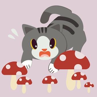 El lindo gato se asusta con una gran cantidad de hongos rojos.