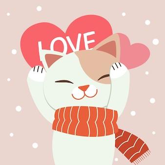 El lindo gato usa una bufanda roja que contiene un gran corazón rosado en el fondo rosado y la nieve blanca.