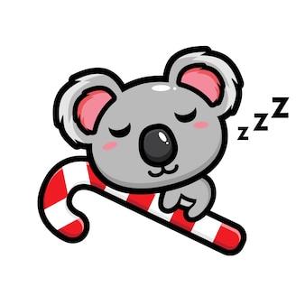 Lindo koala está durmiendo en un bastón de caramelo