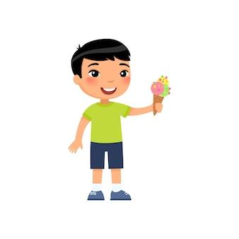 Lindo muchacho asiático con helado sosteniendo helado refrescante en cono de galleta