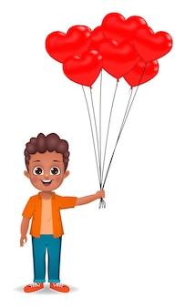 Lindo niño africano sosteniendo globos en forma de corazón