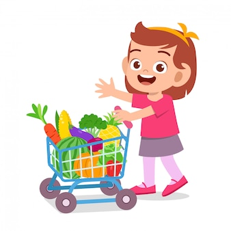Lindo niño feliz comprando frutas y verduras