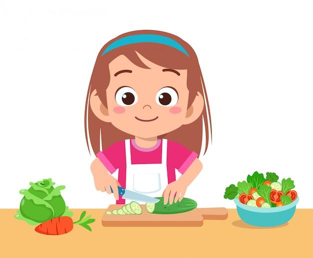 Lindo niño feliz cortando verduras