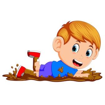 Lindo niño jugando en el barro