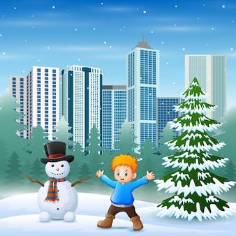 Lindo un niño y un muñeco de nieve en el fondo del parque de la ciudad nevada