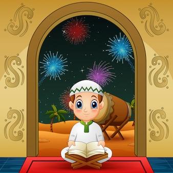 Lindo niño musulmán pequeño leyendo el corán en la noche