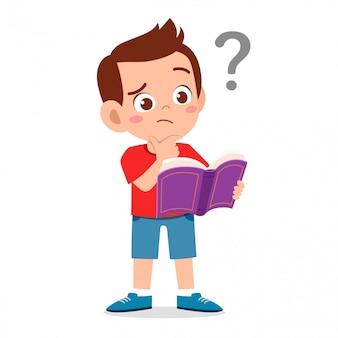 Lindo niño niño lee libro y confundido con signo de interrogación