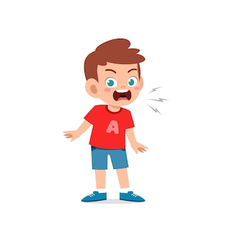 Lindo niño pequeño se para y muestra expresión de pose enojada