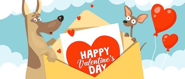 Lindos perros graciosos pastor y chihuahua sostienen un sobre de san valentín en sus patas