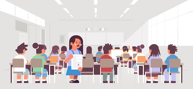 Llorando colegiala sosteniendo papel de prueba fallido con mala vista trasera grado grupo de alumnos sentados en el aula durante la lección concepto de educación interior de la sala de clase moderna