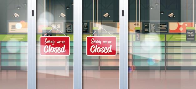 Lo siento, estamos cerrados cartel colgando fuera de la tienda de comestibles con estantes vacíos cuarentena pandémica coronavirus