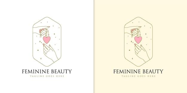 Logotipo de belleza boho con corazón colgante de mano femenina
