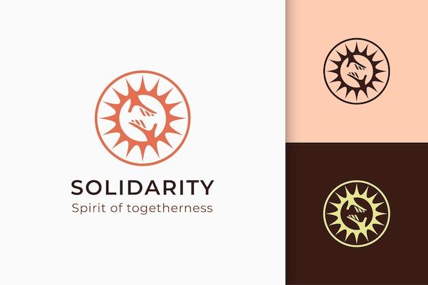 Logotipo de caridad o donación en la mano y el sol representan la paz o la solidaridad.
