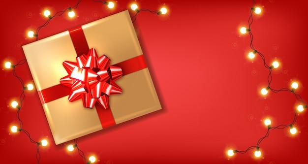Luces y caja de regalo de lazo rojo