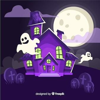 Luna llena detrás de una casa embrujada