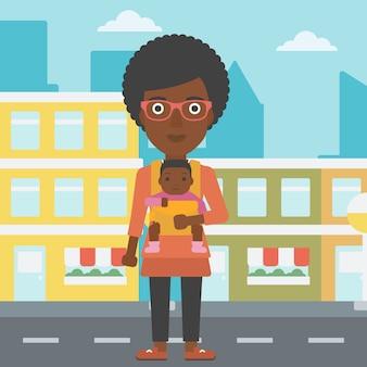 Madre cargando a su hijo en cabestrillo.