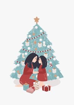 Madre e hija se aferran a los cangrejos de río junto al árbol de navidad con regalos