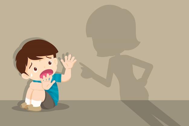 Madre enojada regaña asustado niño sentado en el piso