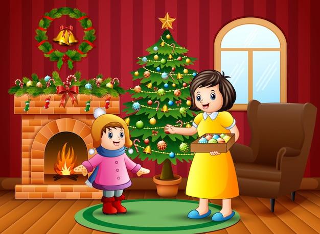 Madre y niña quieren decorar un árbol de navidad.