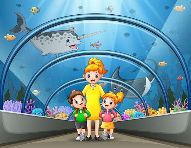 La madre y los niños caminan a través del museo submarino