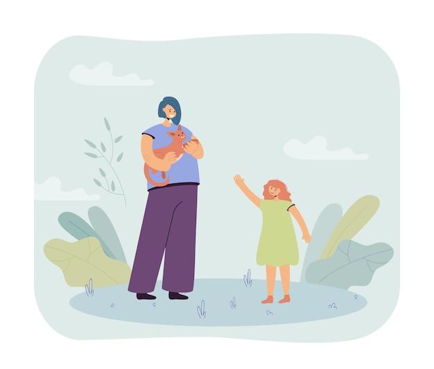 Madre sosteniendo gato en manos e hija de pie junto a ella
