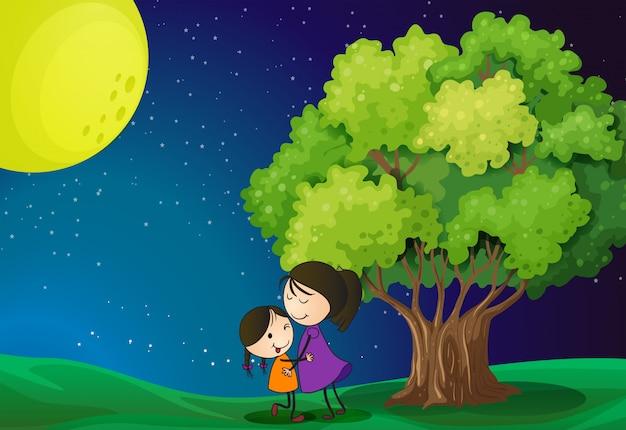 Una madre y su hija cerca del árbol.