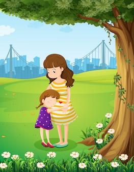 Una madre y su hija debajo del árbol.