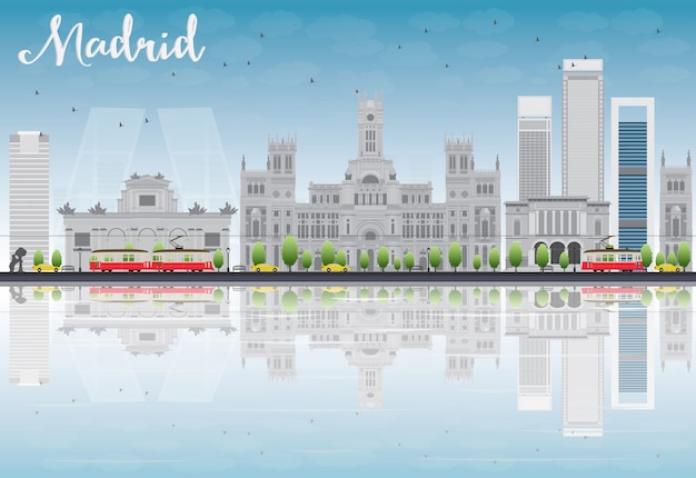 Madrid skyline con edificios grises, cielo azul y reflejos.