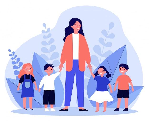 Maestra de kindergarten caminando con niños