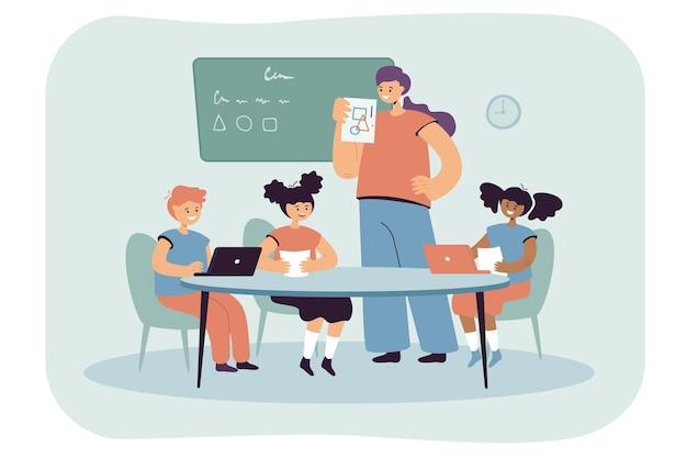 Maestra mostrando a los niños imágenes con formas geométricas