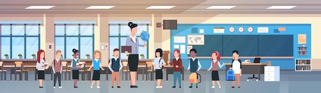 Maestra mujer con grupo de estudiantes de raza mixta en el aula, alumnos diversos en aula moderna en la escuela