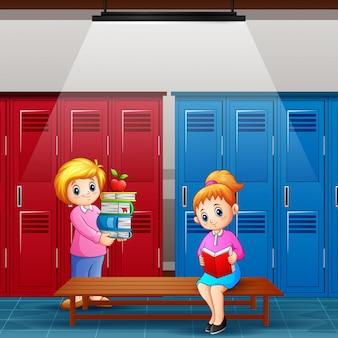 Maestra con niña está leyendo un libro en el vestuario