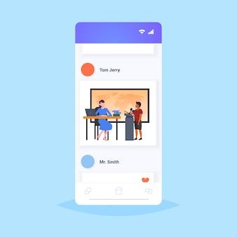 Maestro con alumno alumno hablando en el mapa del mundo lección de geografía en el concepto de educación escolar aula moderna pantalla completa del teléfono inteligente aplicación móvil en línea