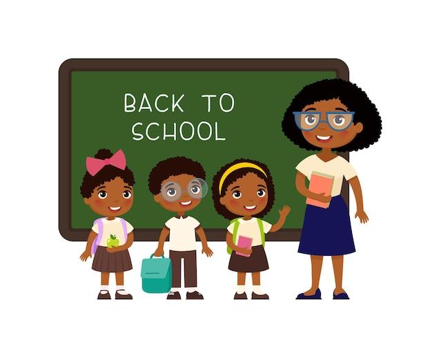 Maestro saludando a los alumnos en el aula niños y niñas vestidos con uniforme escolar y maestra