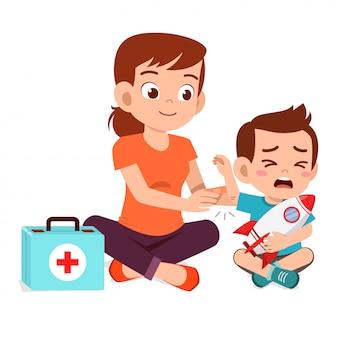 Mamá ayuda primeros auxilios al niño pequeño