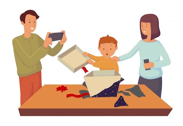 Mamá y papá miran a su pequeño hijo abrir una caja de regalo