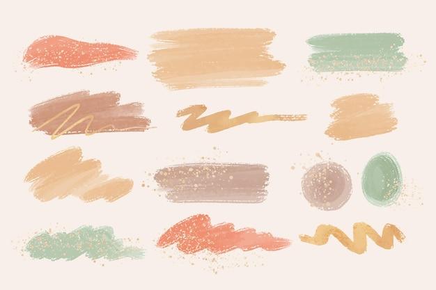 Manchas de acuarela pintadas a mano y trazos de pincel con oro y brillo.