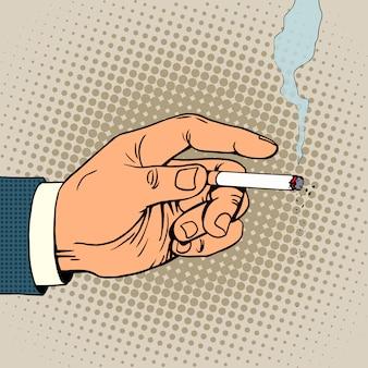 De la mano con un cigarrillo humeante