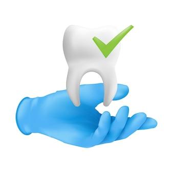 Mano de dentista con guante quirúrgico protector azul sosteniendo un modelo de cerámica del diente.