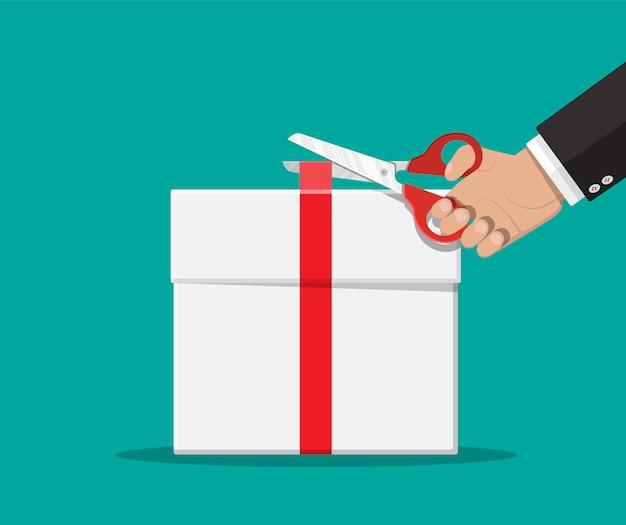 La mano desata el arco de la cinta en la caja de regalo blanca.