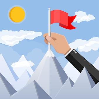 La mano del empresario pone la bandera en la cima de la montaña.