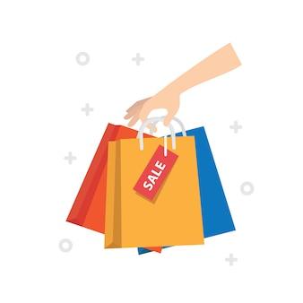 Mano femenina que sostiene bolsos de compras coloridos