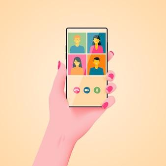 Mano femenina con un teléfono en el que se inicia una videoconferencia o una videollamada grupal. iconos con caras de personas.