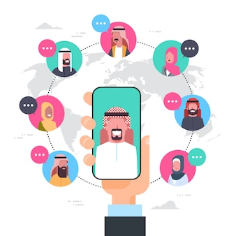 Mano de hombre árabe sosteniendo teléfono inteligente red comunicación concepto grupo de personas árabes conexión sobre mapa mundial