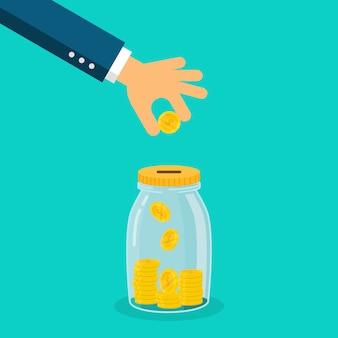 Mano del hombre de negocios que pone la moneda en el tarro del dinero aislado en fondo azul.