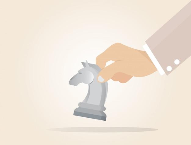Mano de hombre de negocios que sostiene el pedazo del caballero del ajedrez.